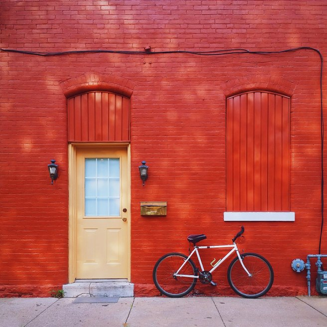 White bike learning on a red building